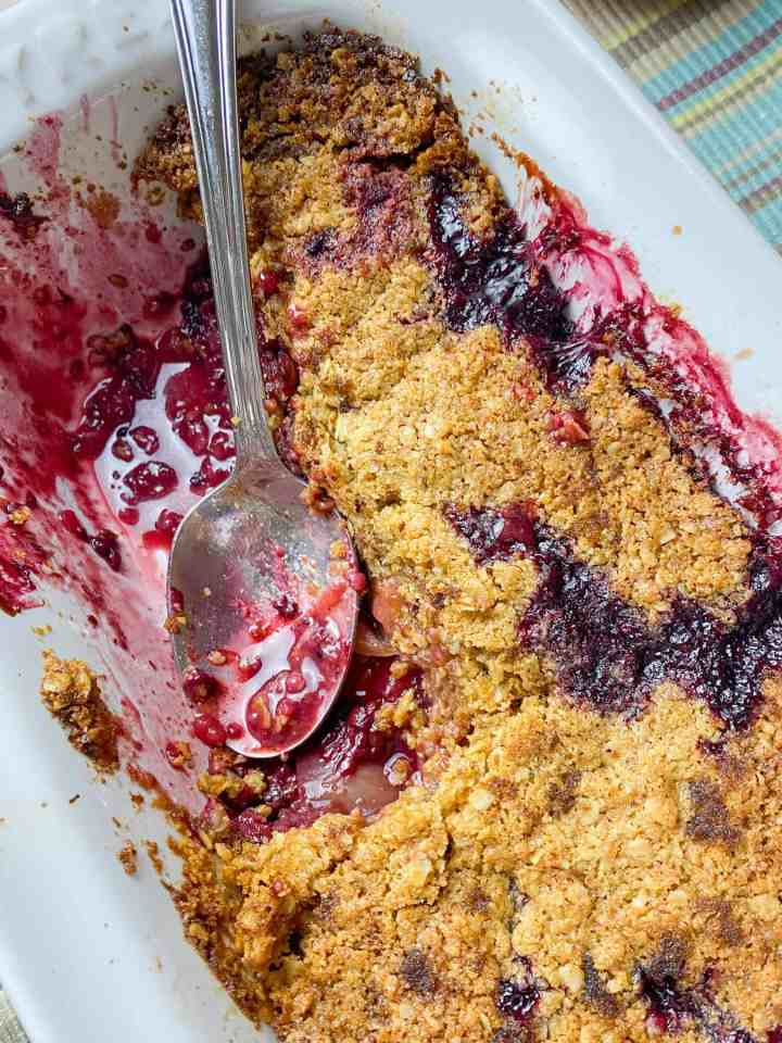 Photo of a white oven dish with some of crumble removed and a spoon sitting in the purple blackberry juices.