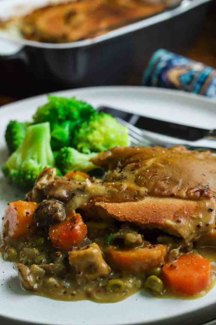 Close-up photo of a serving of vegan pot pie with broccoli on a white plate with cutlery and the main dish in the background.