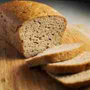 a loaf of vegan gluten free bread with three slices cut and fallen flat on the chopping board in front of the loaf showing the open crumb inside.