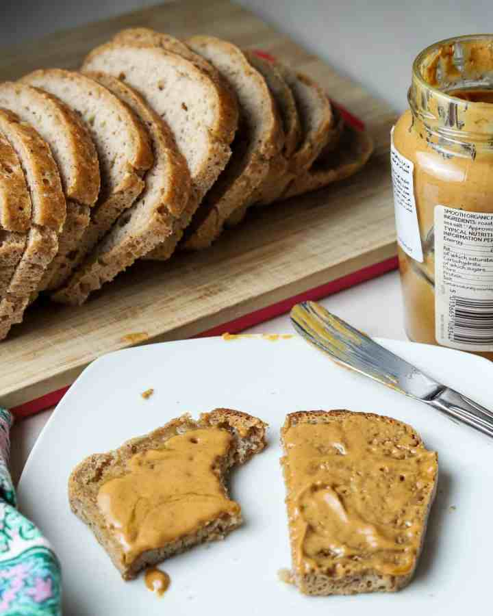 photo of a plate with half eaten piece of vegan gluten-free toast with peanut butter, knife, open jar of peanut butter, a loaf of sliced bread in the background.