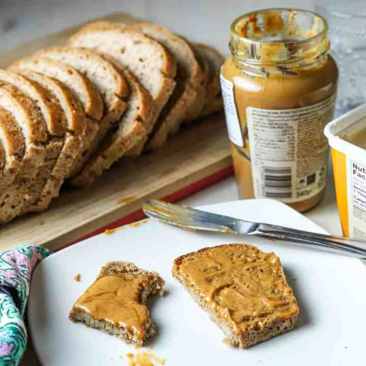 photo of a plate with half eaten piece of vegan gluten-free toast with peanut butter, knife, open jar of peanut butter, open tub of vegan butter, a loaf of sliced bread in the background and a napkin to the side.