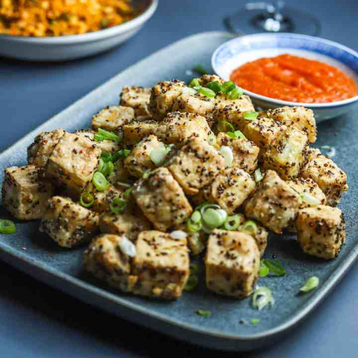 Blue grey plate filled with crispy chia tofu cubes sprinkled with sliced spring onions and served with a little bowl of kimchi sauce.