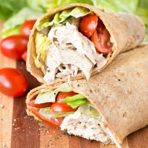 Close up picture of the filling inside a chicken caesar wrap with tomatoes in background