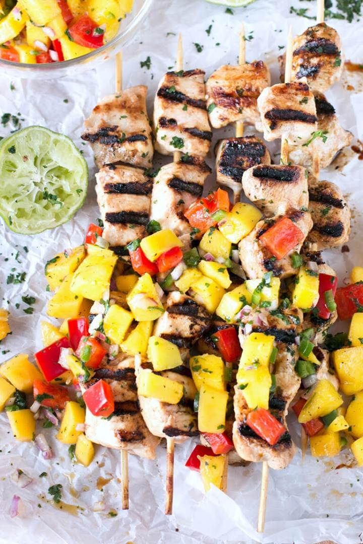 Easy Grilled Mango Chicken Skewers with a fresh mango and pepper salsa are deliciously juicy and packed with flavor. These are great for dinner! #grilledchicken #chicken #mango #chickenkabob