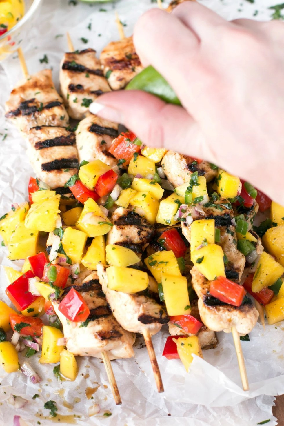 Mango chicken topped with mango salsa and a hand squeezing fresh lime on top