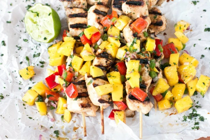 Overhead picture of mango chicken on kabobs with mango salsa and lime