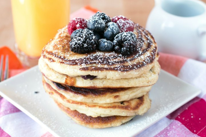 A short stack of buttermilk pancakes topped with mixed berries
