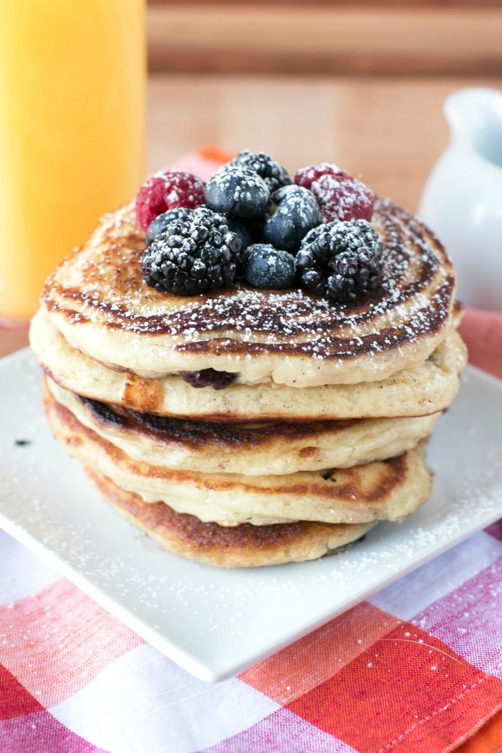 A stack of five mixed berry buttermilk pancakes on a white plate topped with berries and a glass of orange juice in the background