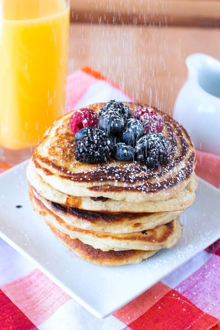 Blackberries, raspberries, and blueberries on top of a stack of pancakes