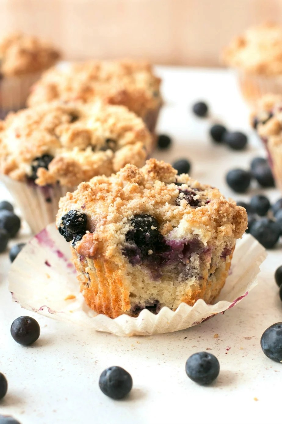 Blueberry crumb muffins sitting on a white surface with one having a bite taken from it