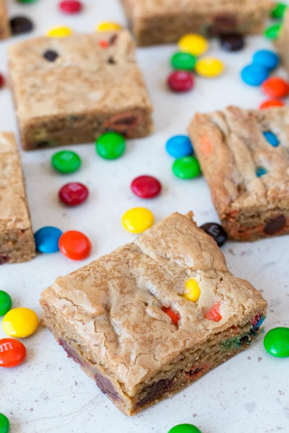 Brown Butter Blondies with M&M's cut into squares and laying on a white surface