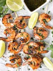 Agave Cilantro Shrimp Skewers with dipping sauce and lime on parchment paper.