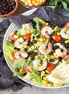 Mexican Shrimp Taco Salad on a white plate surrounded by blue corn tortilla chips
