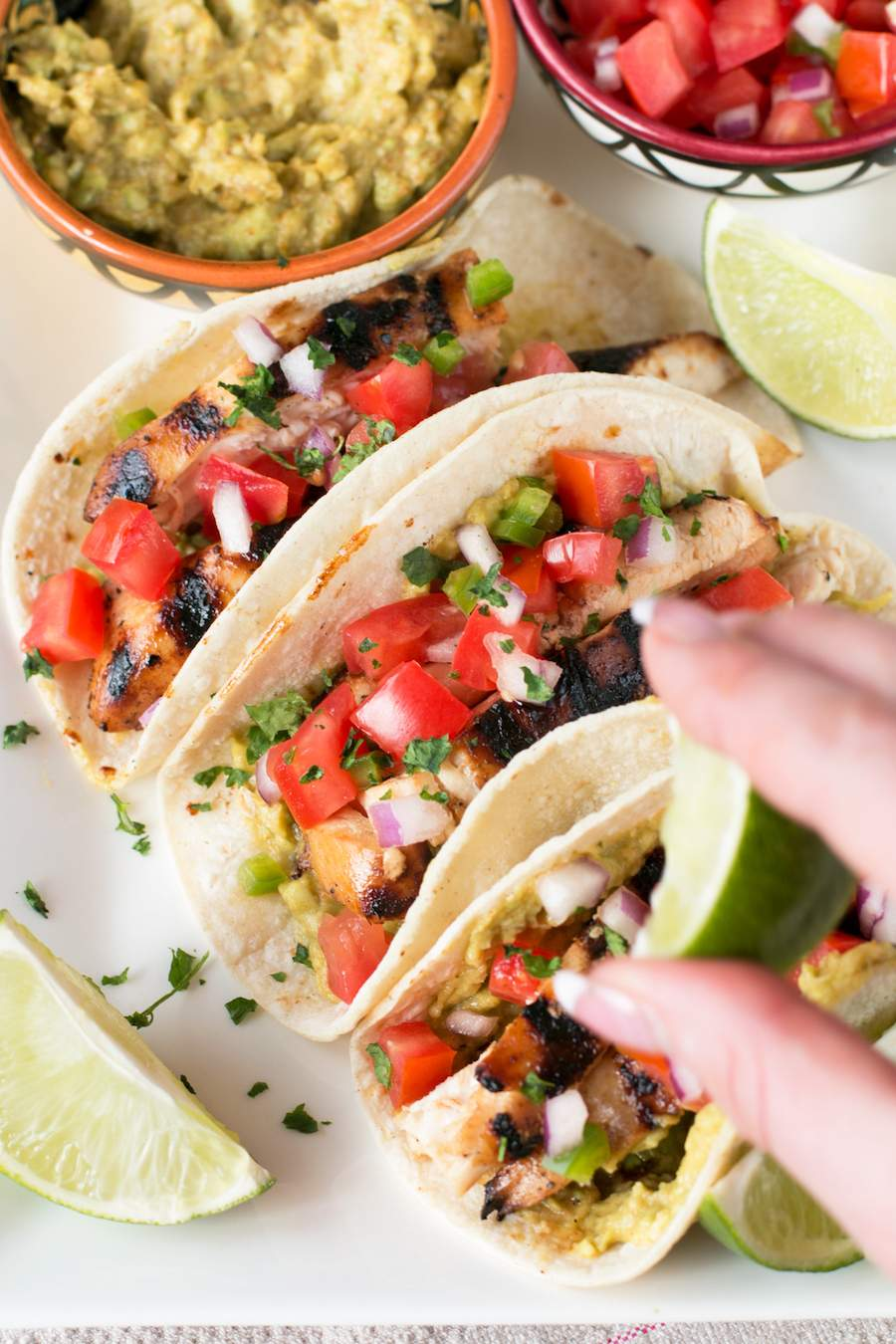 Three Mexican Chicken Tacos with lime and guacamole and tomatoes on a white plate.