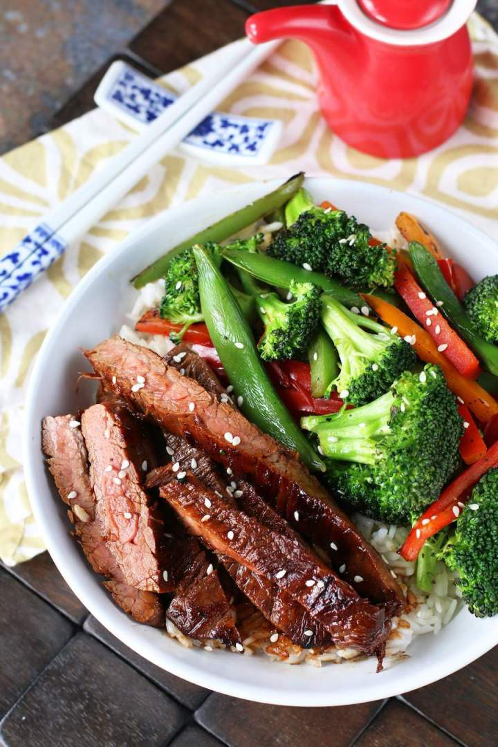 Soy Marinated Flank Steak Stir-Fry in a white bowl with white and blue chopsticks on a white and brown napkin