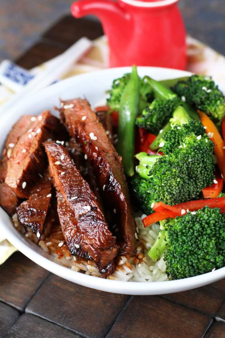 Image of Soy Marinated Steak Stir-Fry in a white bowl with broccoli and a red soy sauce container.