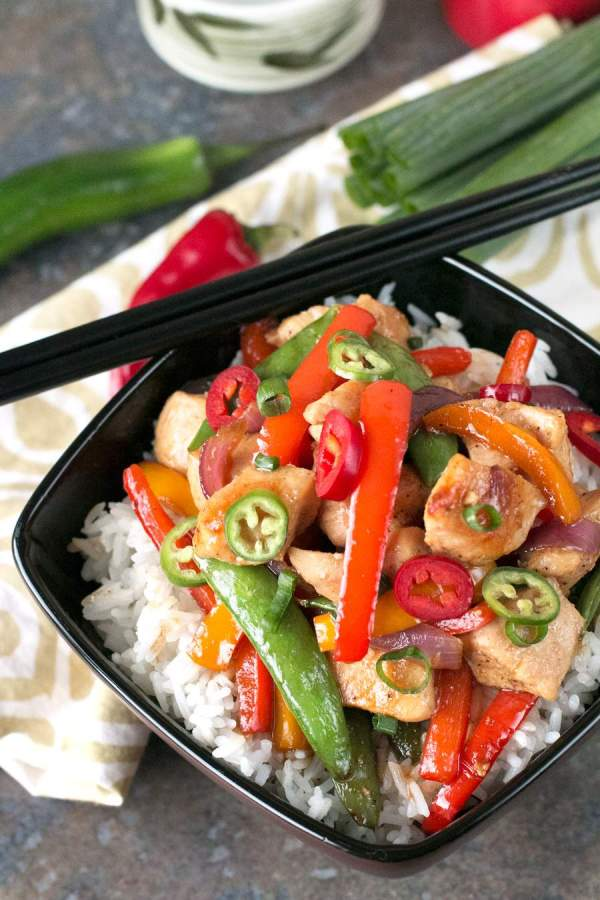 Black bowl with Sweet and Spicy Chicken Stir Fry on a white and brown napkin with green onion and jalapeno peppers.