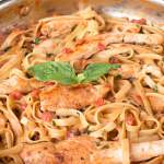 Tomato Basil Chicken Pasta recipe in a copper skillet with tomato and basil in the back.
