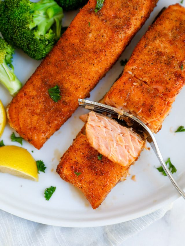 Top down shot of fork cutting into salmon fillets.