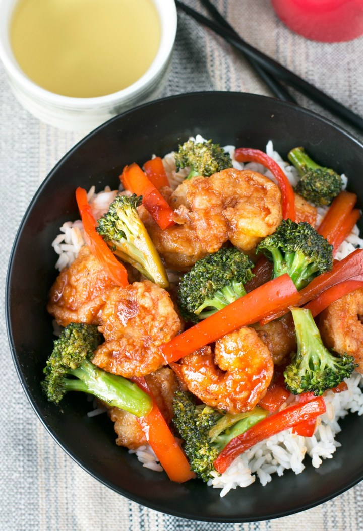 Overhead picture of a large black bowl filled with honey sriracha shrimp stir fry and rice