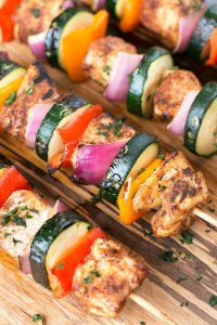 Seasoned vegetable and chicken kabobs on a wooden platter