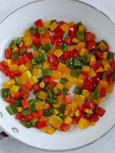 A skillet with red, yellow, and green diced bell peppers cooking.