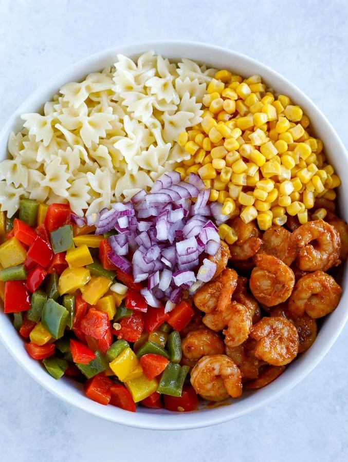 A large white bowl with bow tie pasta, corn, shrimp, bell peppers, and diced red onions.