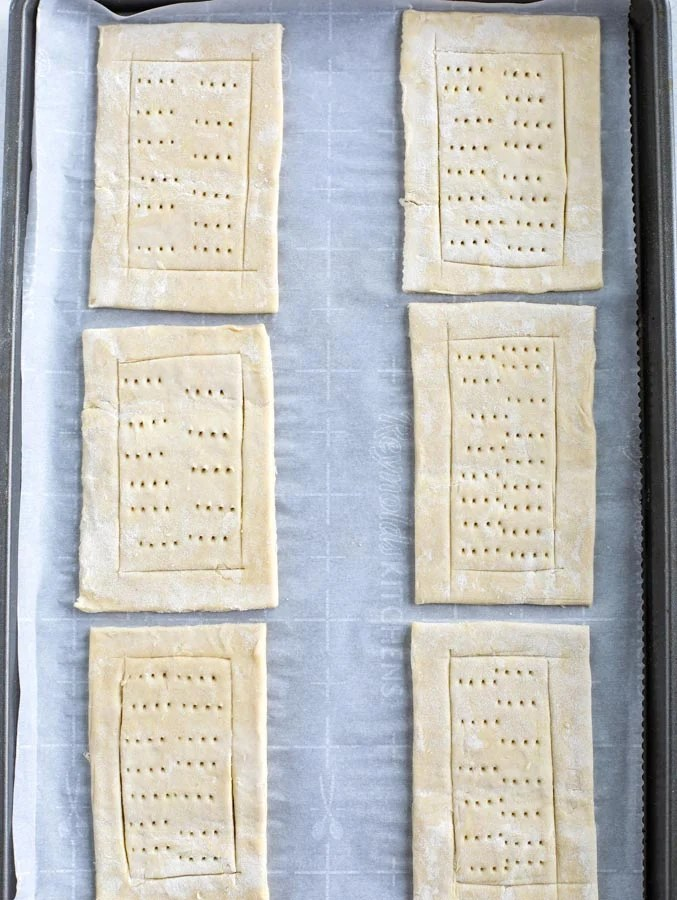 A baking sheet covered with parchment paper with 6 rectangles of puff pastry cut and poked.