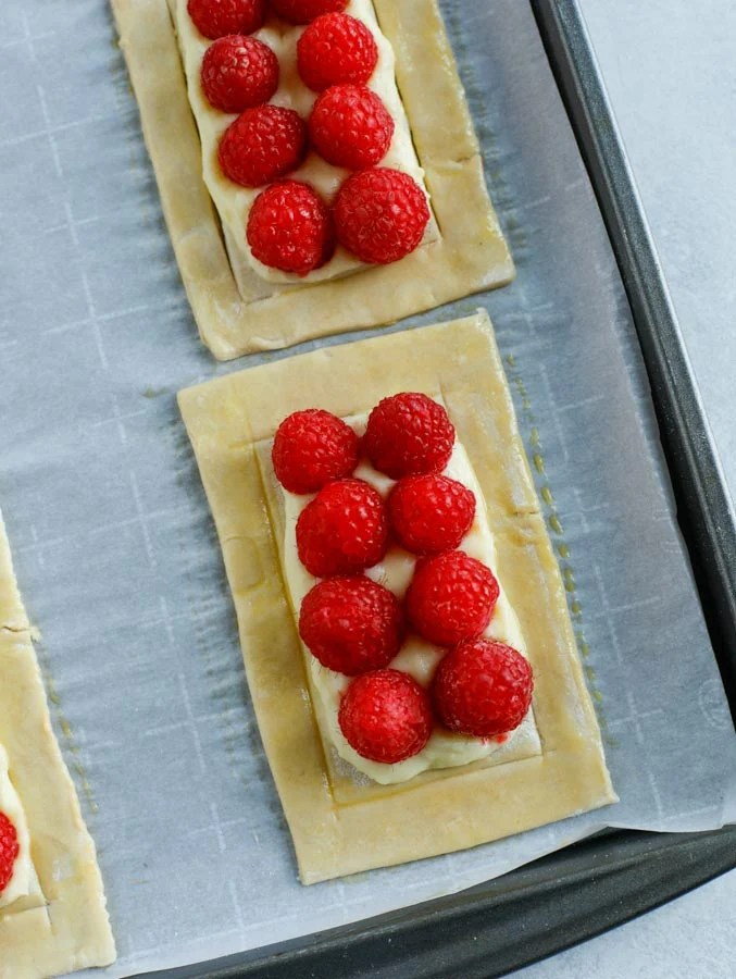 A close up shot of uncooked raspberry puff pastry rectangles on a parchment paper lined baking sheet.