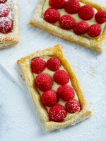 Three raspberry puff pastry tarts on a counter dusted with powdered sugar.