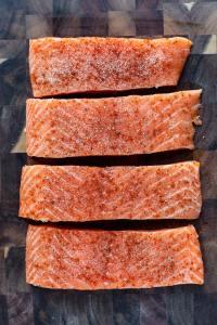 4 raw salmon fillets on a cutting board.