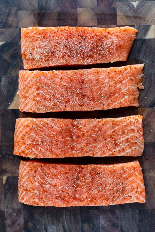 4 raw salmon fillets on a cutting board.