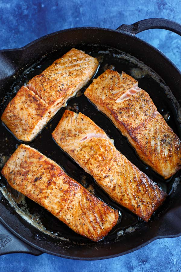 A cast iron skillet with 4 salmon fillets cooking on a blue counter.