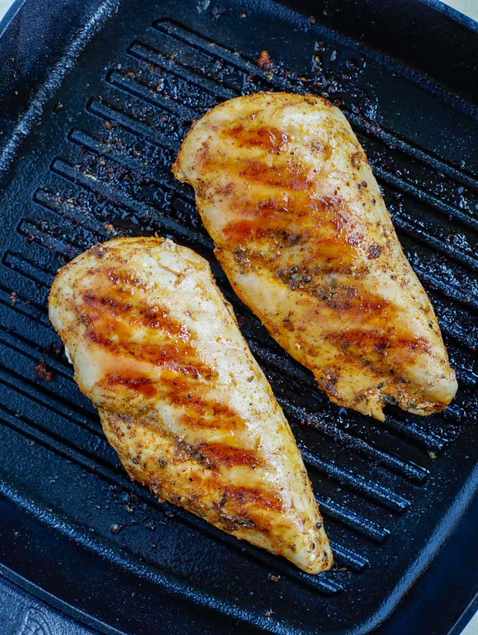 Marinated chicken cooking in a grill pan.