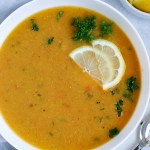 Lebanese lentil soup served in a white bowl and garnished with lemon wedges and parsley