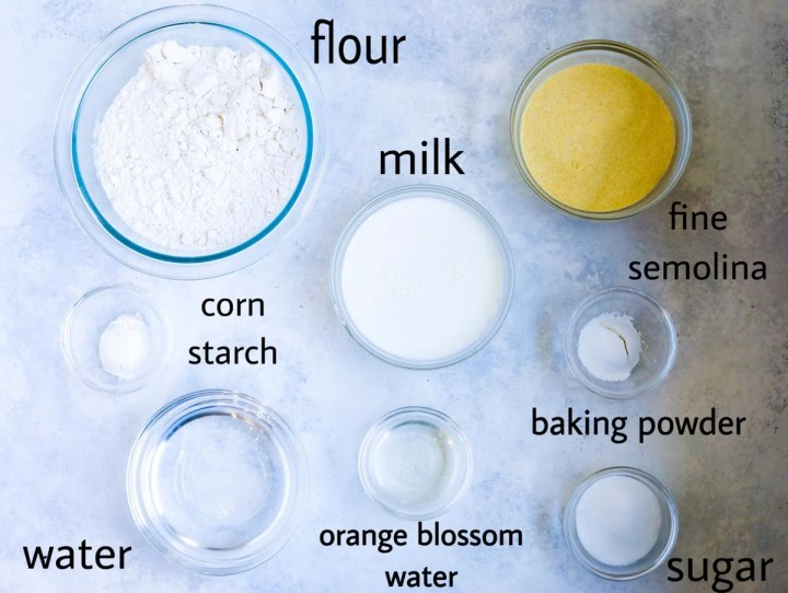 Atayef pancake ingredients laid out on a table. flour, milk, fine semolina, corn starch (optional) baking powder, sugar, water and orange blossom water.