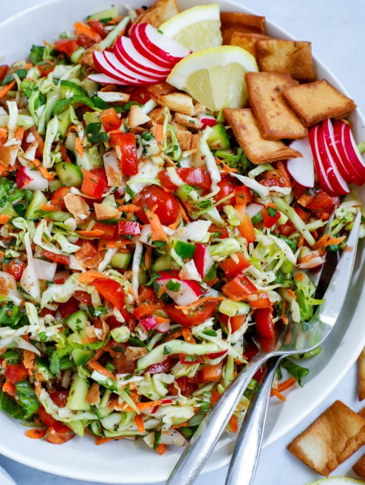Cabbage fattoush salad in a bowl with serving spoons