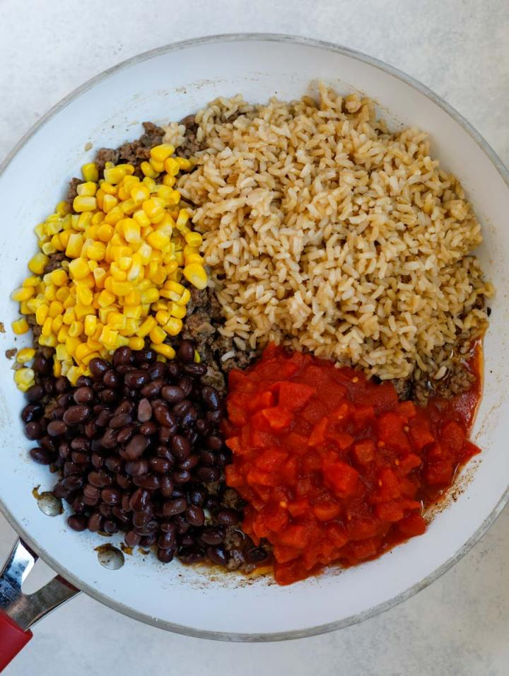 beans, tomatoes, rice and corn in a skillet.