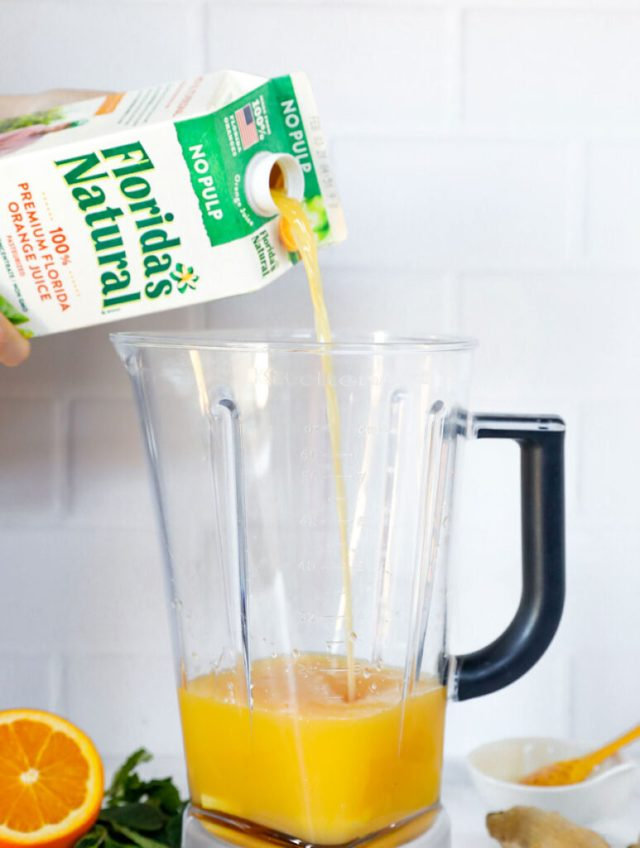 ingredients in the blender with orange juice being poured into the blender