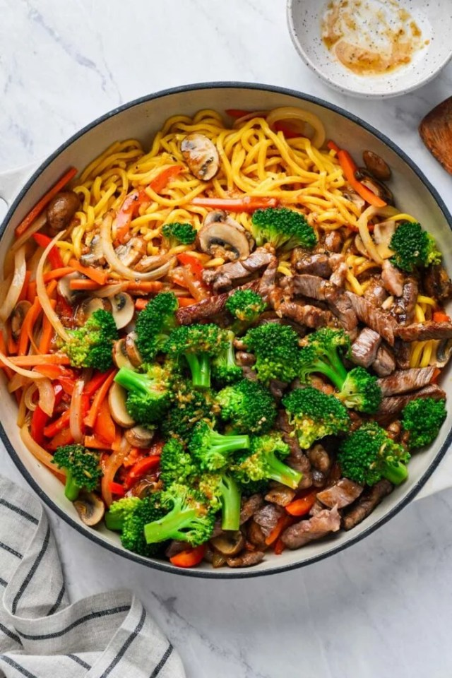 beef lo mein ingredients in a skillet ready to be mixed with sauce