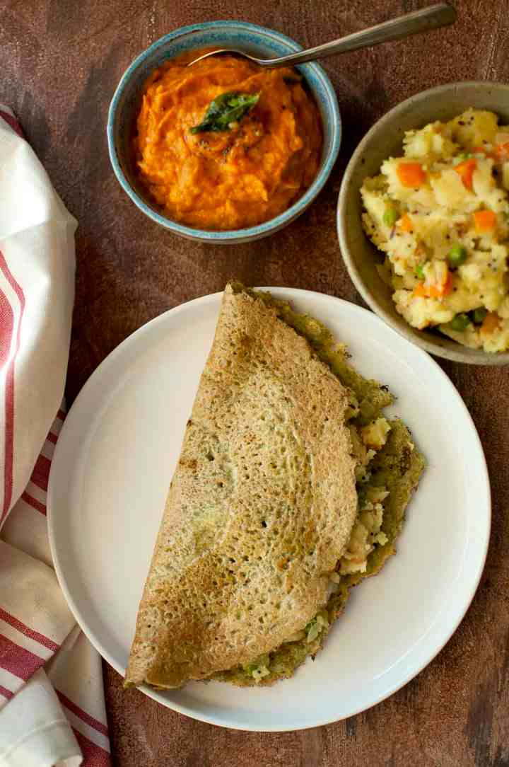 White plate with pesarattu upma with a blue bowl of chutney and bowl of upma