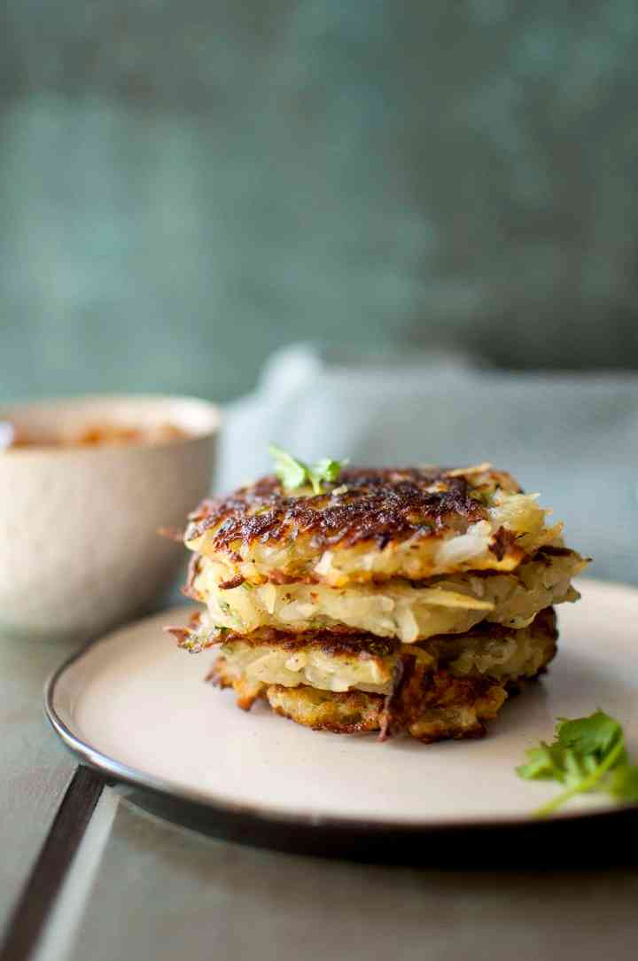 White plate with crispy potato latkes topped with parsley