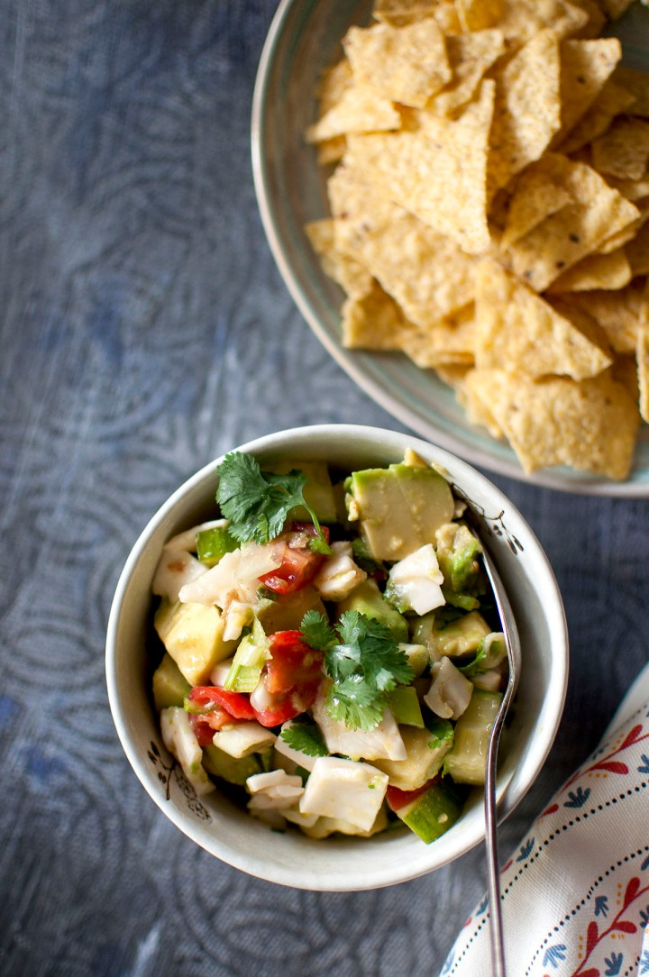 White bowl with chopped cucumber, avocado, tomatoes, coconut, cilantro and blue plate with tortilla chips
