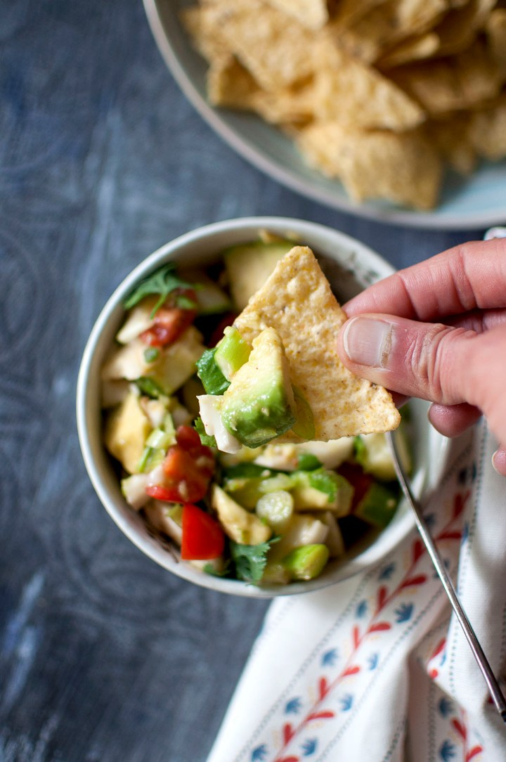 Hand holding a tortilla chip topped with coconut ceviche