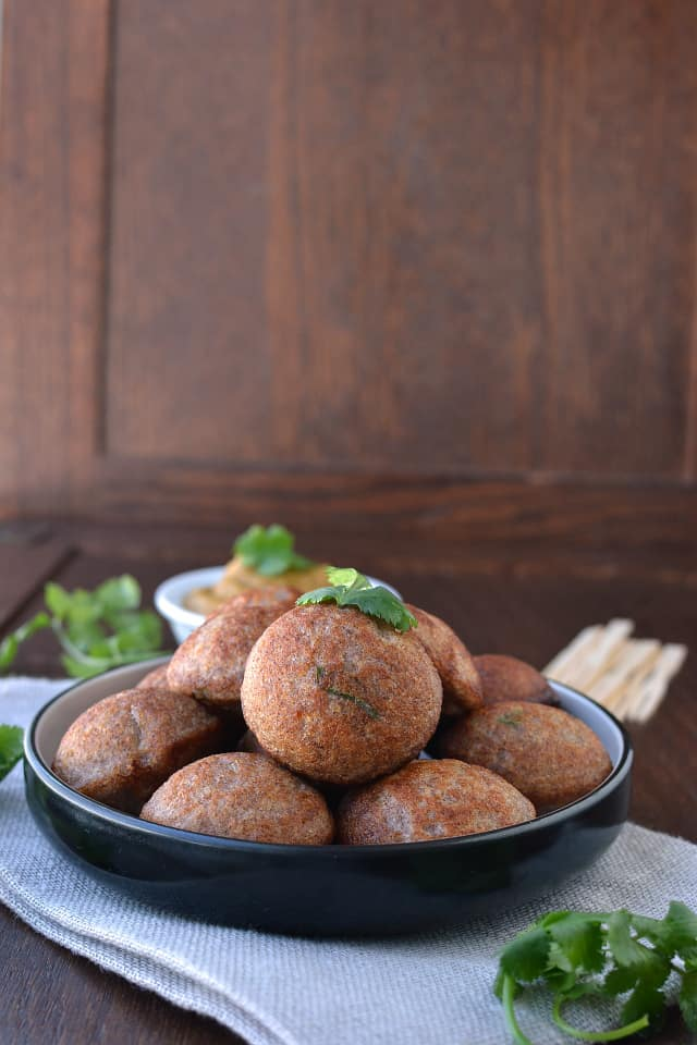 Black ceramic plate with south indian style aebleskivers and cilantro
