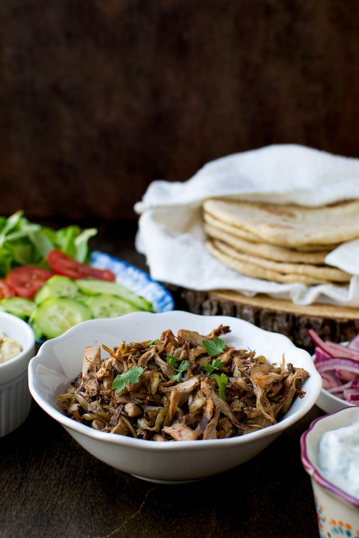 White bowl with jackfruit and flatbreads in the background