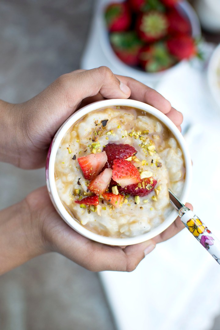 Hands holding a bowl with Almond rice pudding topped with strawberries and chopped nuts