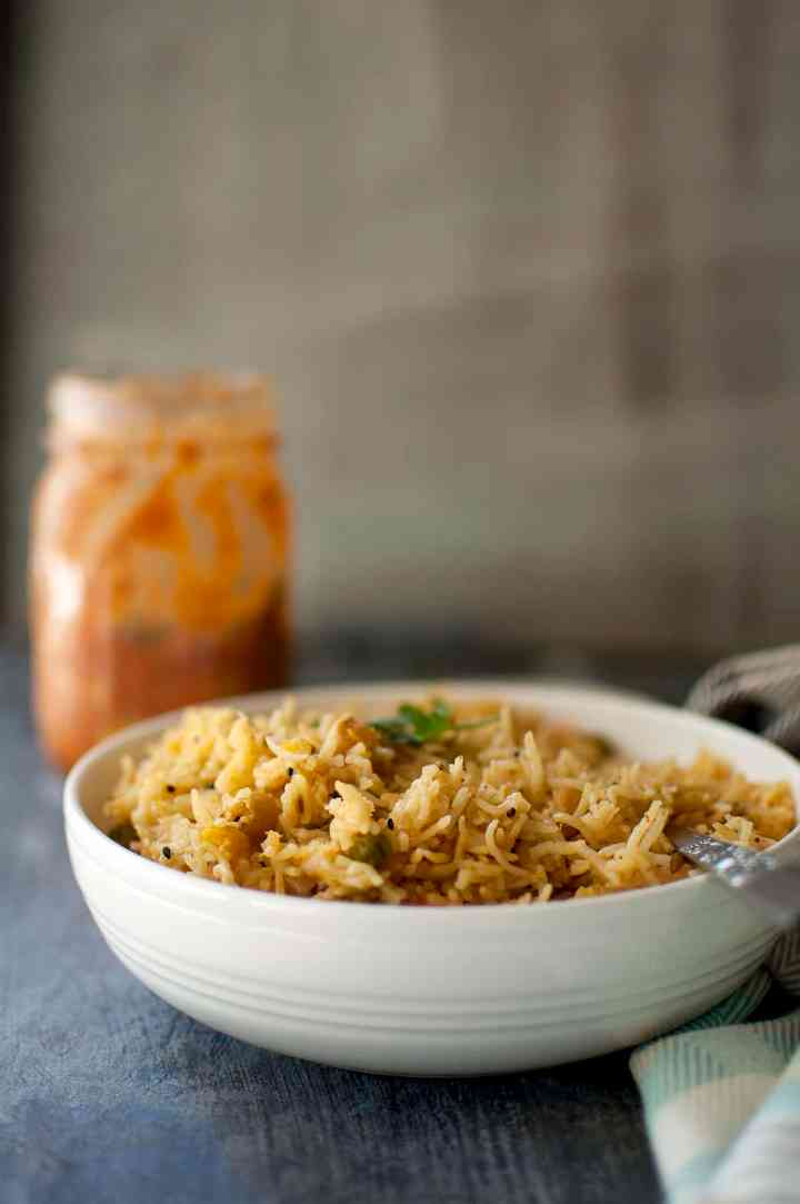 White bowl with achari vegetable pulao with a jar of pickle in the background