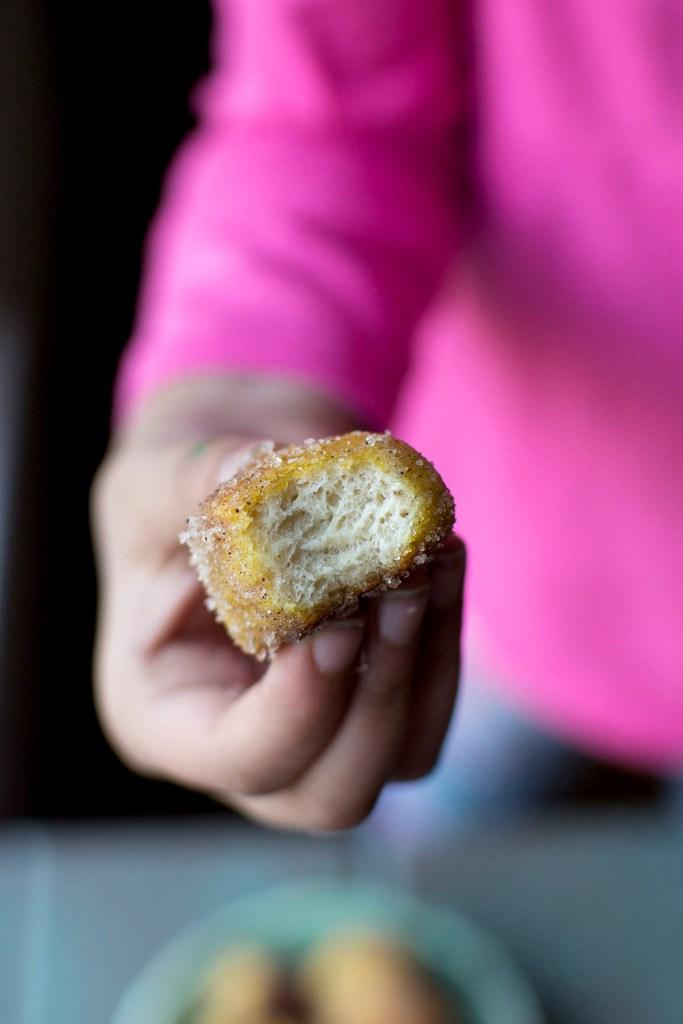 Little girl holding a bitten cinnamon sugar pretzel bites