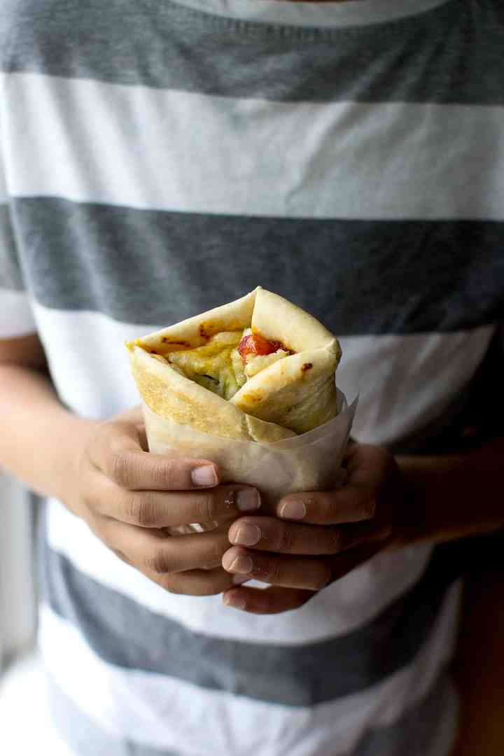 Person holding a folded Turkish Lahmacun pizza